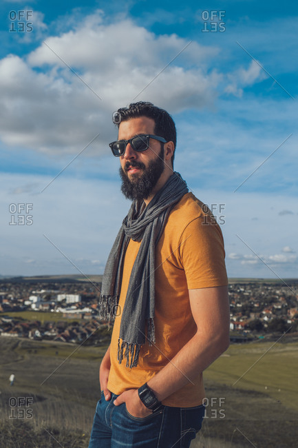 Side view of confident young ethnic bearded guy in trendy outfit and sunglasses resting on hilly terrain against cloudy blue sky