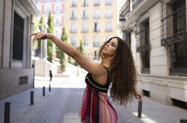 Young fit ethnic female dancer with long curly hair dancing on paved street looking away