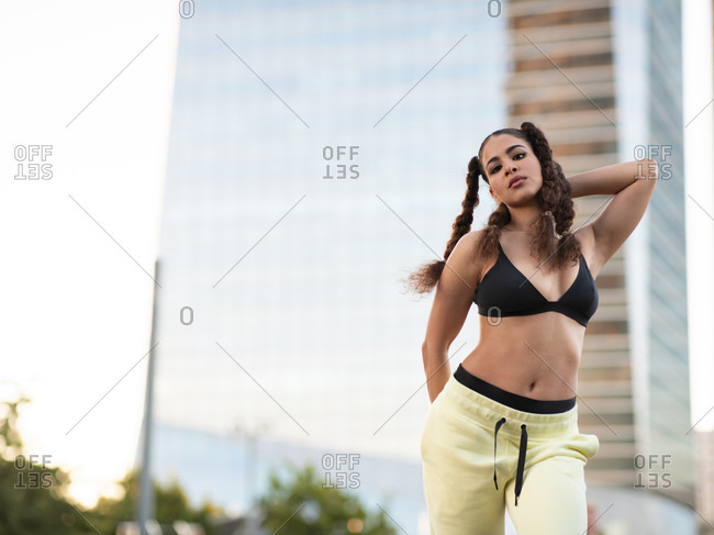 Young self assured slim ethnic sportswoman in bra and pants standing looking at camera in city park with hands in pockets against modern skyscrapers