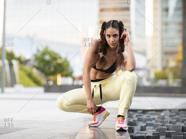 Full length of gorgeous fit ethnic lady in trendy sports bra and sneakers touching curly hair and looking at camera while sitting on haunches in city park