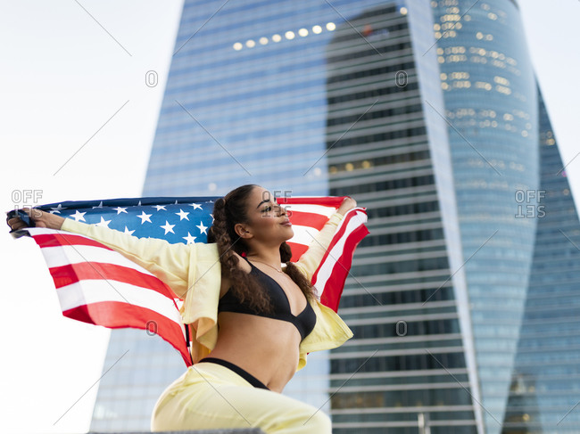 Side view of confident young ethnic lady in sports bra waving American flag and looking away against modern glass skyscraper