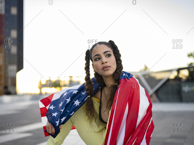 Confident young ethnic lady in sports bra waving American flag and looking away against modern glass skyscraper