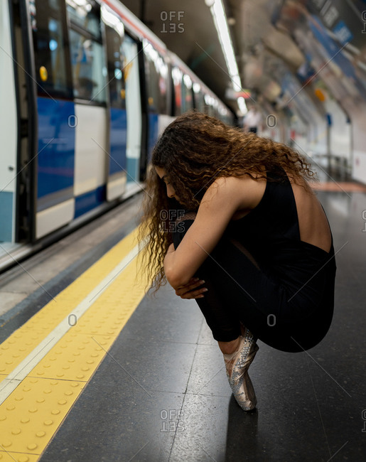 Side view of unrecognizable young ballerina with long curly hair in pointe shoes embracing knees while sitting on haunches in subway station