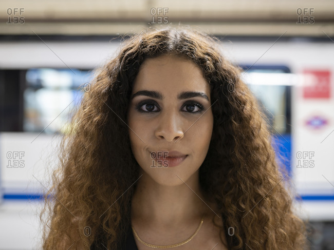 Graceful young ethnic lady with long curly hair standing in underground subway station and looking at camera