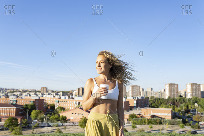 Cheerful young female wearing white sports bra standing with takeaway coffee against modern city buildings on sunny day while looking away with toothy smile
