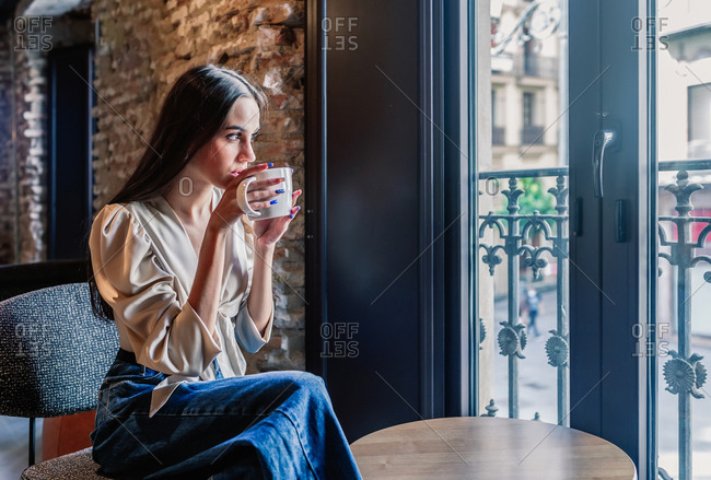 Side view of serene young brunette female in elegant outfit sitting on chair in front of window and drinking coffee in room with stylish interior