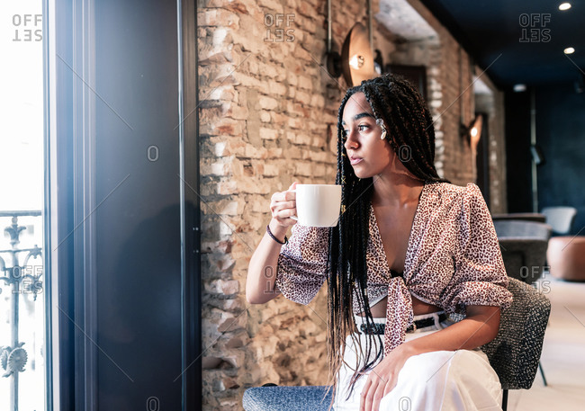 Modern millennial African American female in stylish outfit enjoying cup of hot aromatic coffee while resting in modern loft cafe