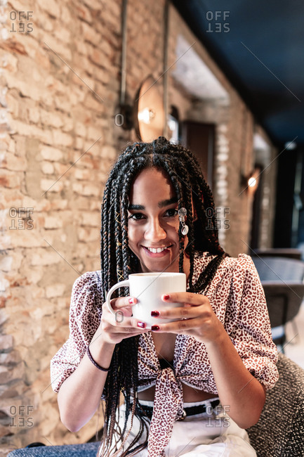 Modern millennial African American female in stylish outfit enjoying cup of hot aromatic coffee while resting in modern loft cafe looking at camera