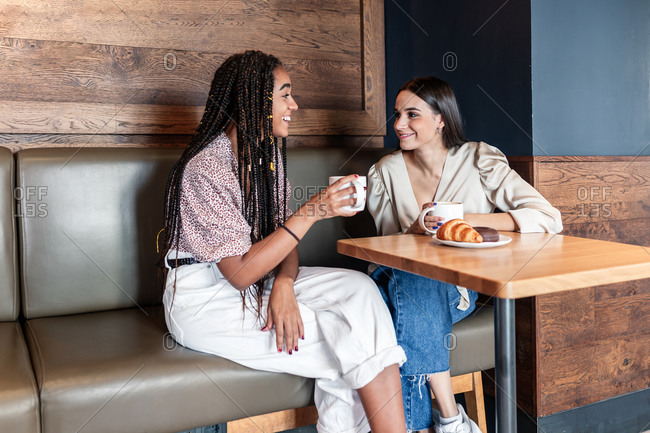 Cheerful young multiracial women in trendy outfits drinking coffee and chatting happily while spending time together in modern cafeteria