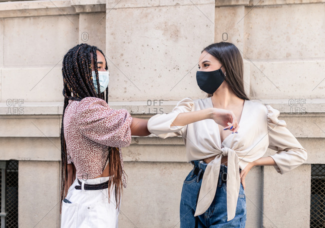 Side view of positive young multiracial female friends in trendy clothes and protective masks greeting each other with elbow bump on city street during coronavirus pandemic