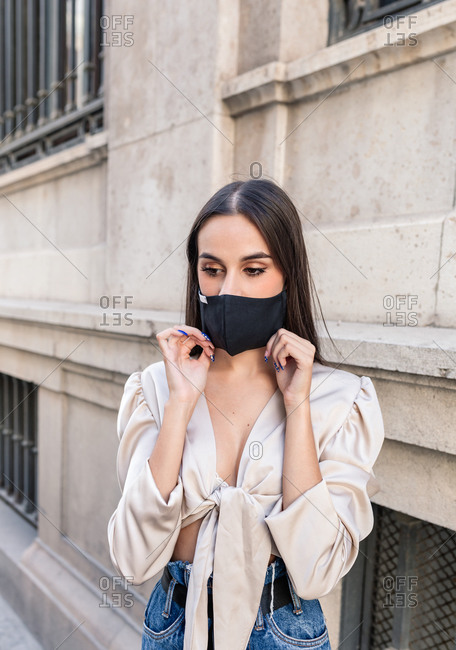 Calm stylish female standing on street and putting on protective mask during COVID 19 outbreak in city while looking down