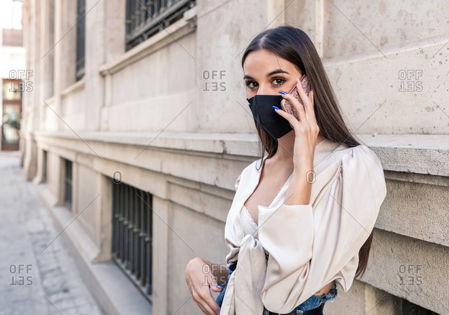 Young female in stylish apparel and protective mask standing near stone building in city and having conversation via smartphone during coronavirus epidemic and looking at camera