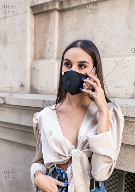 Young female in stylish apparel and protective mask standing near stone building in city and having conversation via smartphone during coronavirus epidemic and looking away
