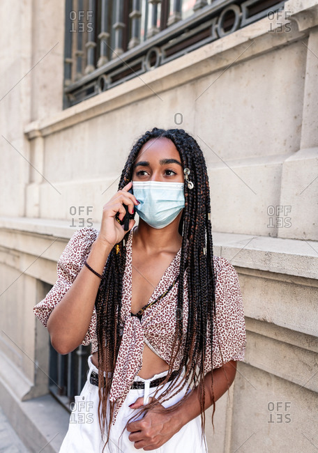 Thoughtful African American female in medical mask speaking on cellphone while standing in city during coronavirus epidemic and looking away