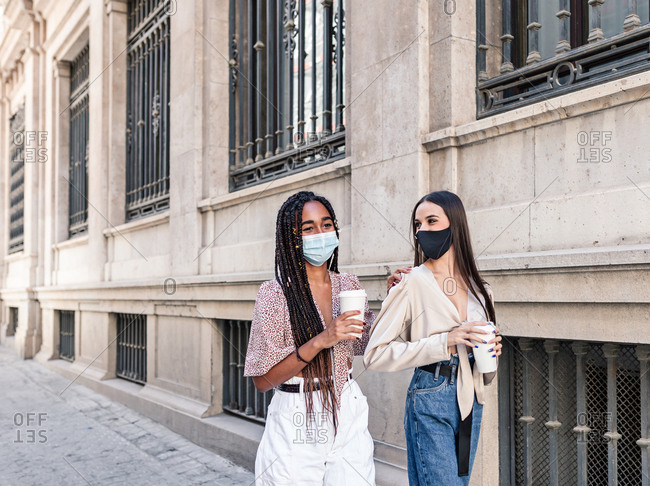 Side view of positive multiethnic female friends in masks and with takeaway coffee walking along street and spending weekend together in city during coronavirus epidemic