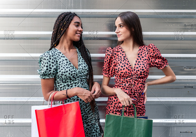 Charming multiracial female friends in similar stylish dresses standing with paper bags in city after shopping and looking at each other