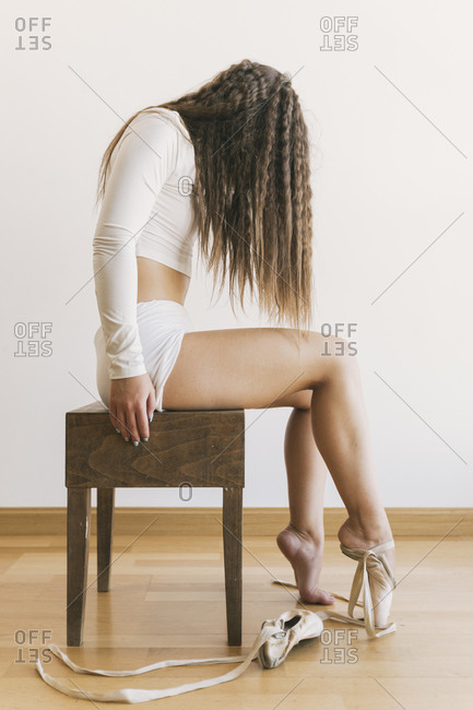 Side view of unrecognizable confident ballerina in pointe shoes sitting on stool in studio on white background