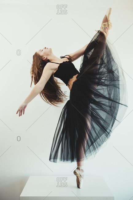 Side view of graceful female ballet dancer in pointe shoes and black tutu standing on stool on tiptoes with closed eyes and outstretched arms while balancing and performing dance in studio