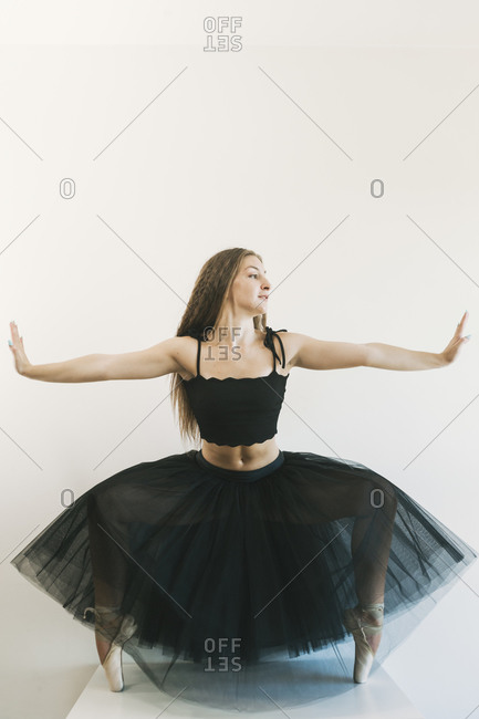 Graceful female ballet dancer wearing black tutu standing in pointe shoes on tiptoes in dance position on white background and looking away