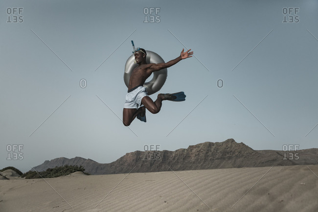 Low angle full body of young African American male with diving equipment and inflatable ring jumping above sand against gray sky