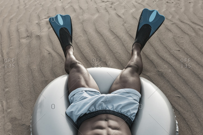 From above of crop anonymous black male in diving flippers lying on inflatable ring on rippled sand