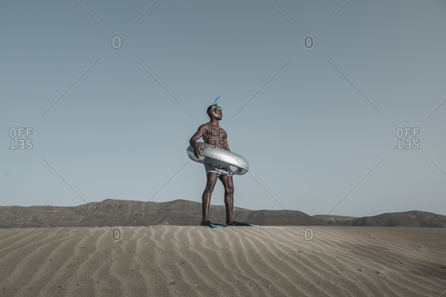 From below black male in diving flippers standing with inflatable ring on rippled sand