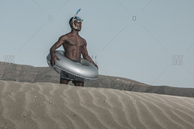 Black male in diving flippers standing with inflatable ring on rippled sand