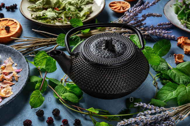 Herbal tea, natural, organic, and healthy, with a tea pot and a variety of ingredients on a blue background