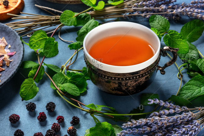 Herbal tea, natural, organic, and healthy, a tea cup with an assortment of ingredients on a blue background
