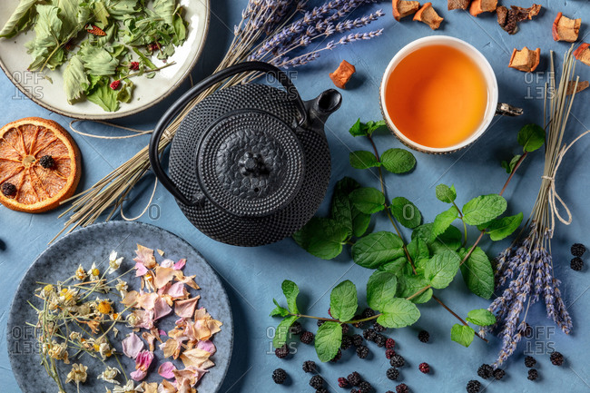Herbal tea, natural, organic, and healthy, a tea pot, cup, and a variety of ingredients, shot from above on a blue background