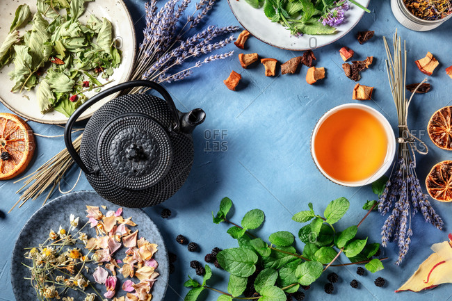 Herbal tea design template with a place for text. A frame of a tea pot, cup, and many natural, organic, and healthy ingredients, top shot