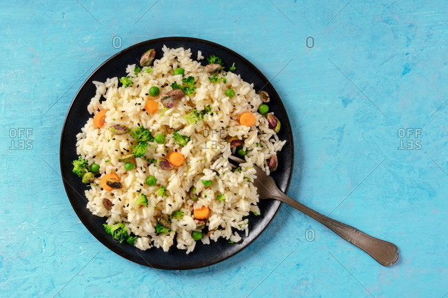 Vegan rice with vegetables, healthy and delicious, shot from the top with copy space on a blue background