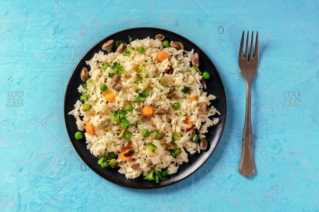 Vegan rice with vegetables, healthy and delicious, overhead shot on a blue background