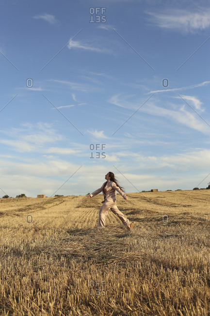 Side view full length stylish female wearing posh suit strolling on grassy agricultural field beneath clear blue sky in countryside