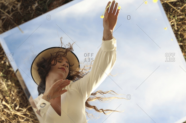 Young serene female wearing stylish white dress and hat standing with eyes closed with arms raised gracefully against clear blue sky and reflecting in square mirror placed on grassy lawn