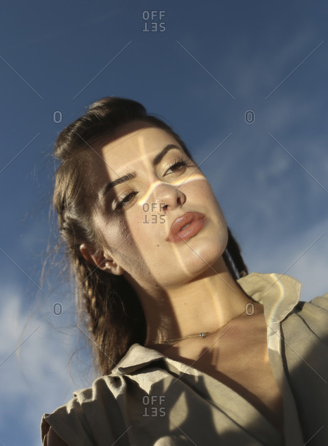 From below of sensual young female model with long hair in trendy outfit looking in mirror against blue sky