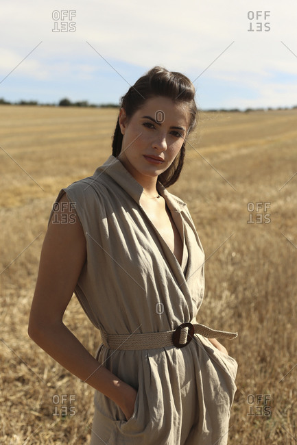 Stylish female wearing posh suit standing on grassy agricultural field beneath clear blue sky in countryside looking at camera