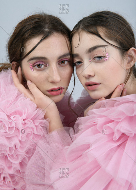 Side view of young tender female models wearing romantic pink chiffon dresses touching faces of each other and looking at camera on gray background in studio