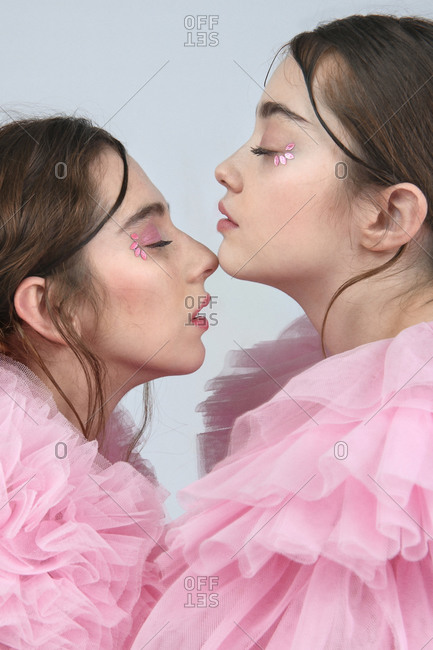 Side view of calm women in pink tulle outfit standing face to face and touching chin and nose gently with closed eyes on gray background in studio