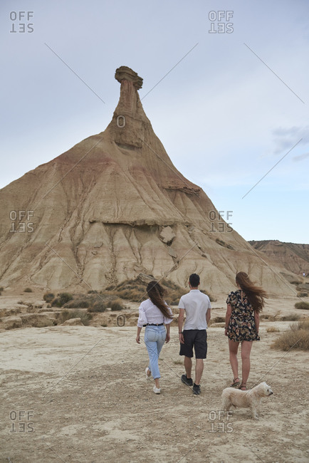 Back view of anonymous young travelers with cute dog walking on sandy terrain towards picturesque hill in located in Bardenas Reales on sunny day