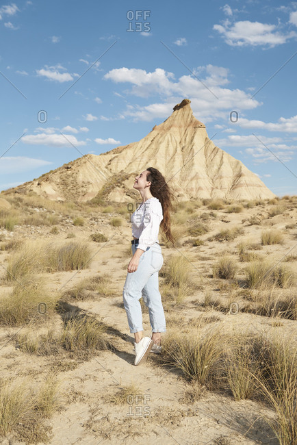 Side view of happy young female traveler relaxing in semi desert terrain during trip in Bardenas Reales located in Spain