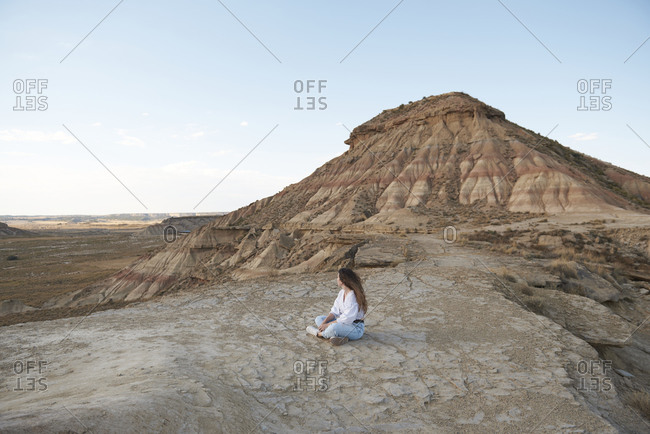 Side view of unrecognizable young female tourist with long hair in casual outfit relaxing on rocky ground near sandy hill on windy day in Bardenas Reales