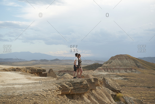 Side view of anonymous young female and male travelers embracing while standing on rocky cliff and admiring amazing scenery of mountains in Bardenas Reales