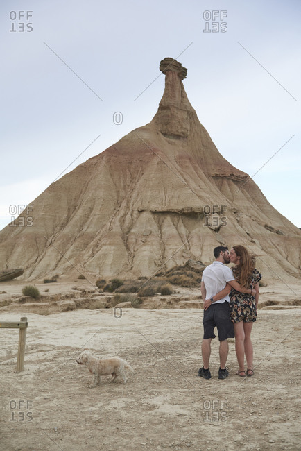 Back view of anonymous young romantic couple hugging and kissing while standing against rocky mountain in Bardenas Reales