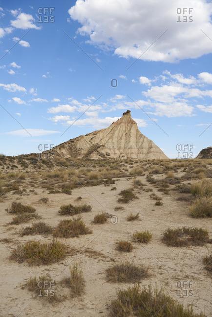 Amazing landscape of badlands in semi desert terrain in Bardenas Reales against cloudy blue sky