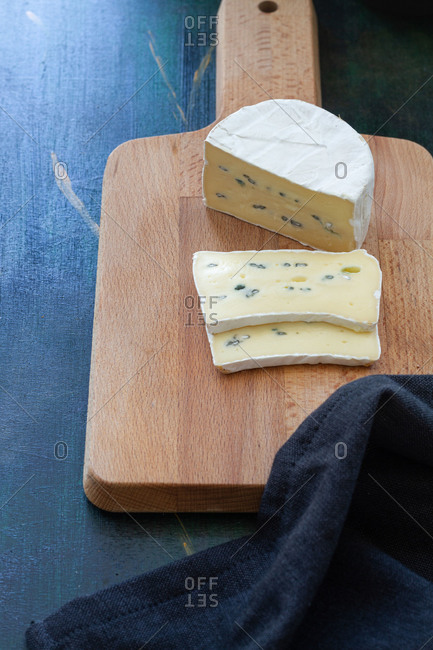 From above composition of soft cheese placed on wooden cutting board near bowl with currant