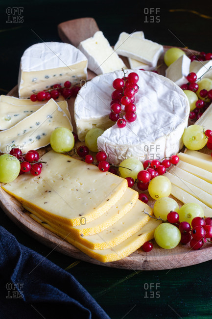 High angle composition of assorted cheese platter including Camembert Parmesan and Mozzarella cheeses sliced and decorated with tasty grapes and red currants