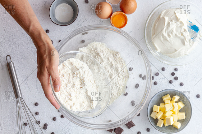 Top view crop faceless cook with whisk in hand above bowl with flour placed on table amidst baking ingredients in kitchen