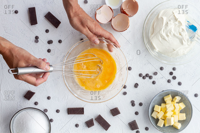 Top view crop unrecognizable cook beating eggs in bowl placed on table with baking ingredients including butter sour cream and chocolate
