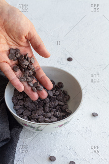 From above crop anonymous person spilling sweet dark chocolate chips into ceramic bowl on table
